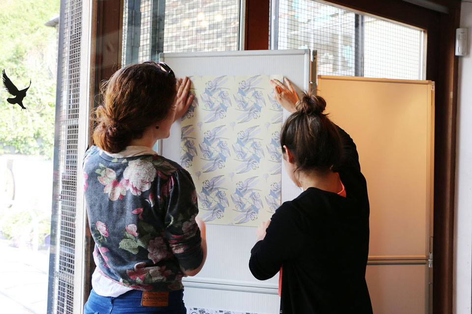 Astrid Jaekel and a student hang the exhibition